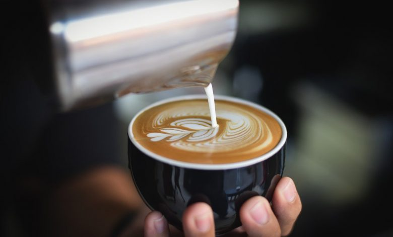 Man pouring frothy milk into a coffee
