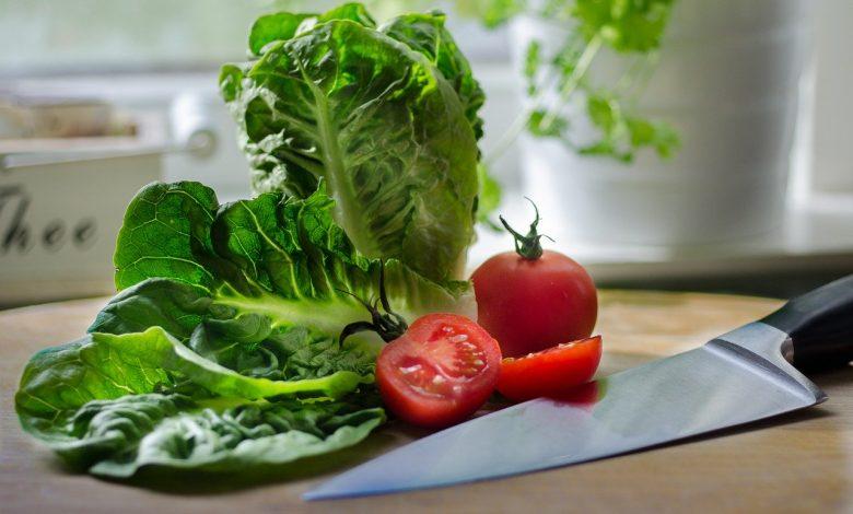 Asharp knife next to a chopped tomato