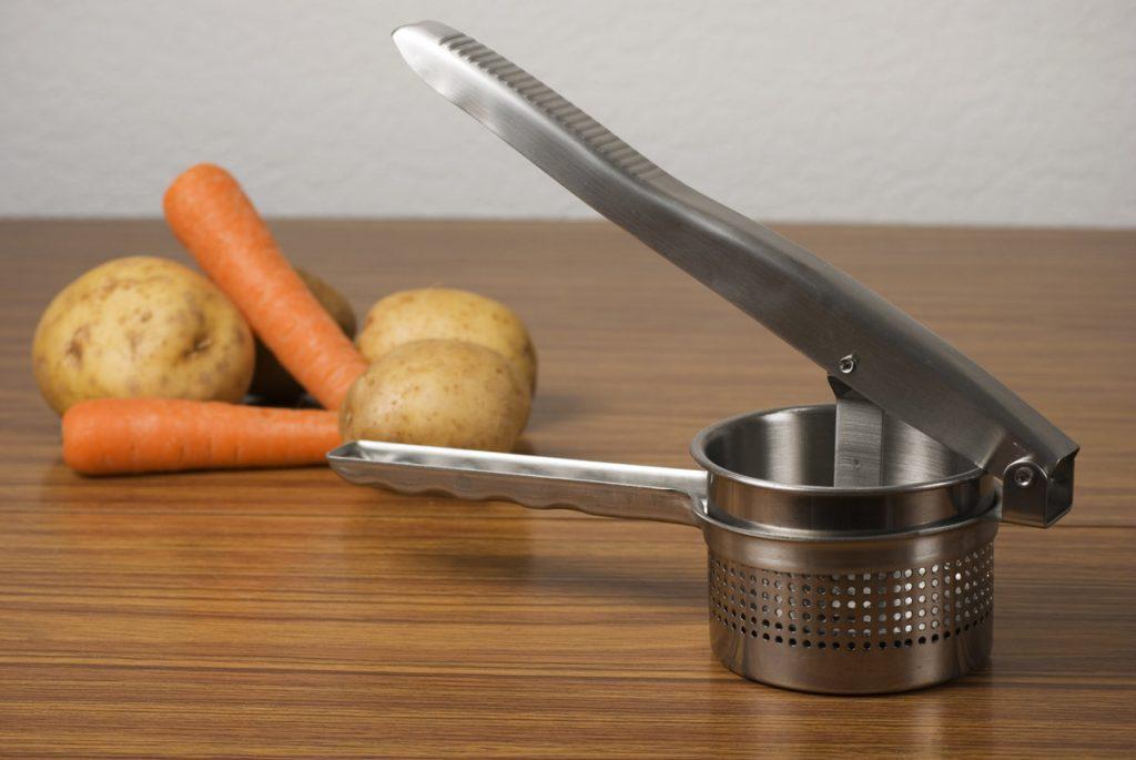 A potato ricer next potatoes and carrots