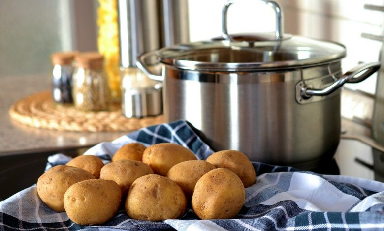 Several potatoes next top a cooking pot